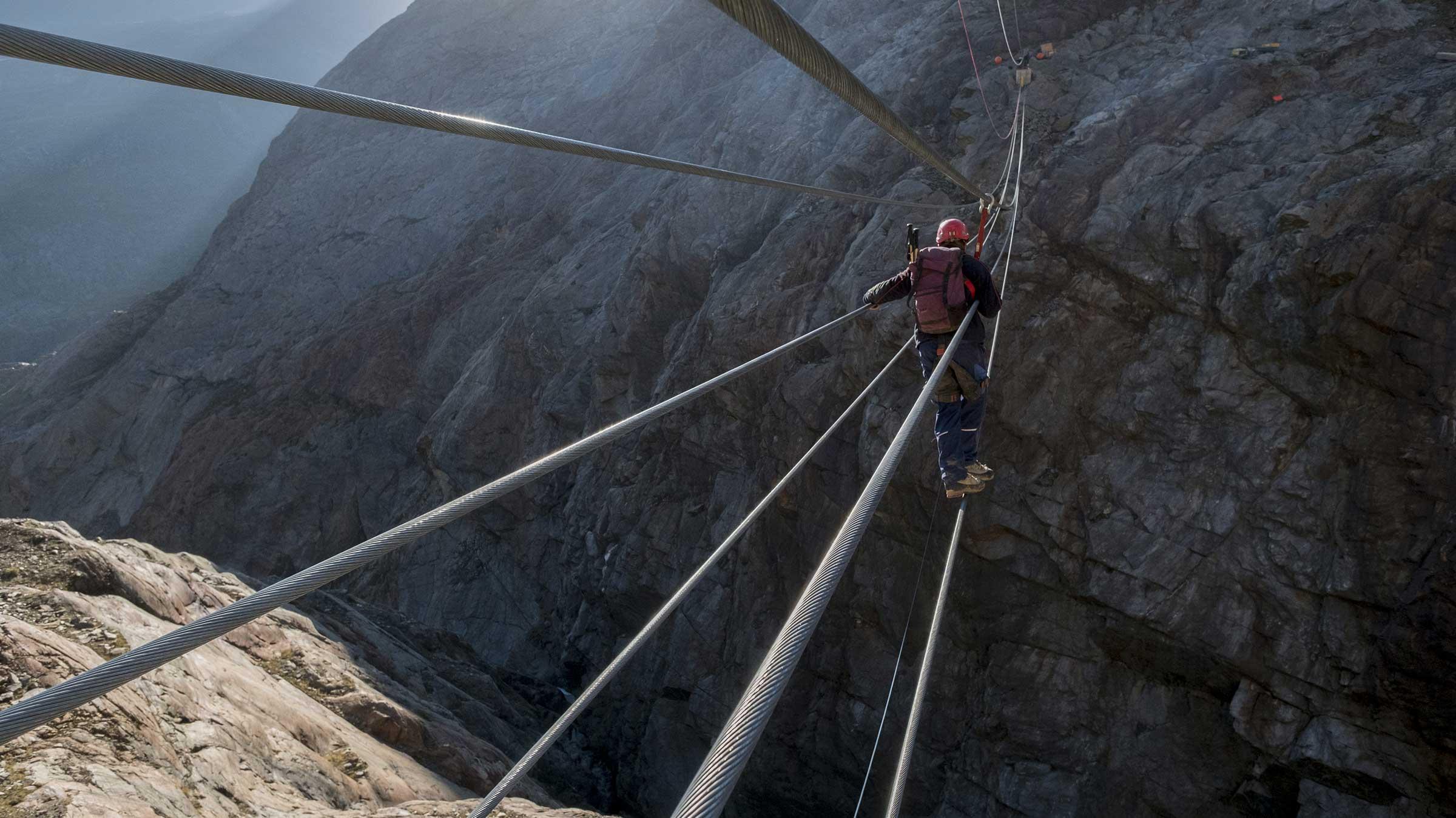 Ein Bauarbeiter balanciert über Stahlseil - Piccard Hängebrücke Obergurgl-Hochgurgl