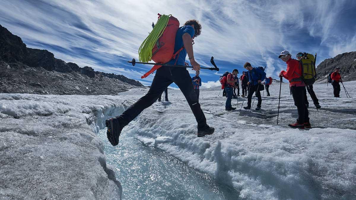 Teilnehmer hüpft über Wasser am Gletscher - Salewa GET Vertical Obergurgl-Hochgurgl